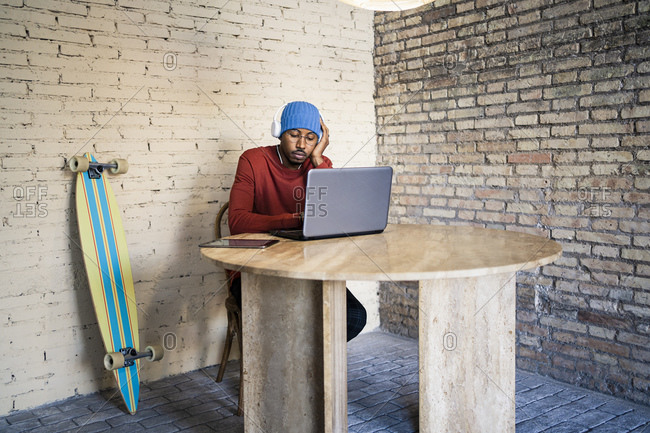 Freelance worker with eyes closed listening music by laptop against white brick wall