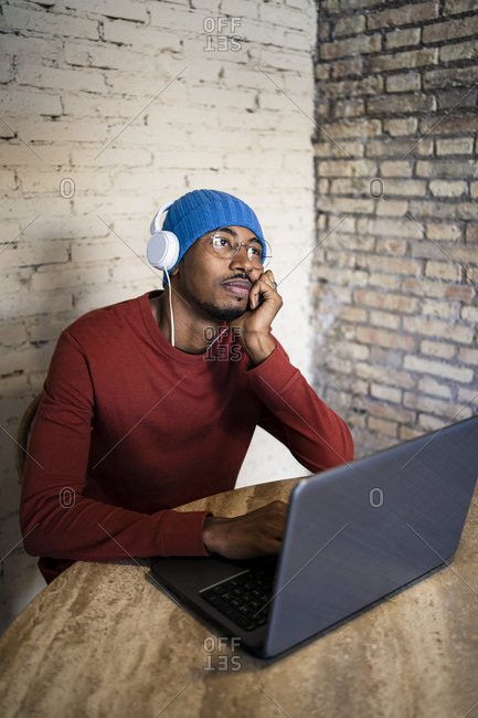 Male entrepreneur day dreaming while listening music by laptop against brick wall