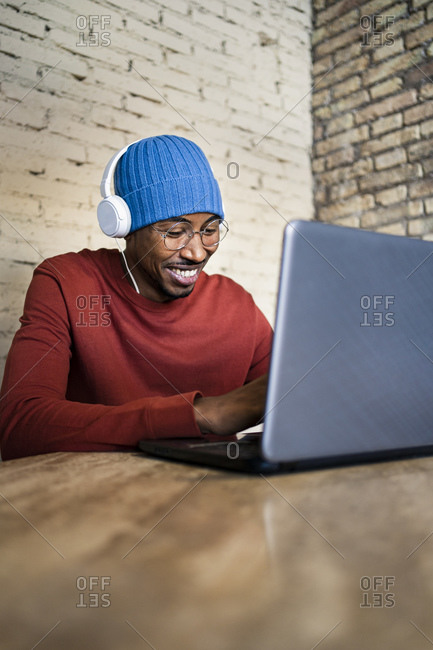 Smiling male professional using laptop while listening music through headphones on table
