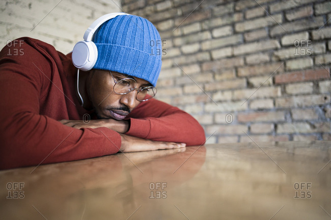 Mid adult man contemplating while listening music through music on table
