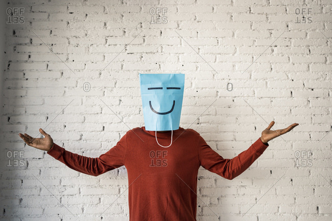 Man with arms raised wearing a paper bag on face against white brick wall