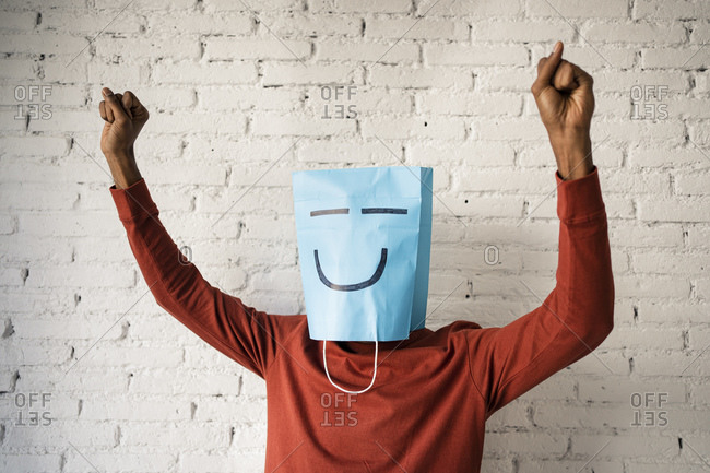 Man wearing blue paper bag while dancing against white brick wall