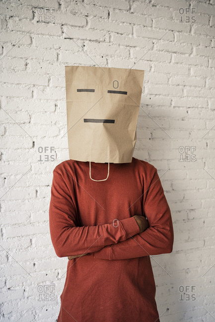 Man wearing paper bag on face with arms crossed against white brick wall