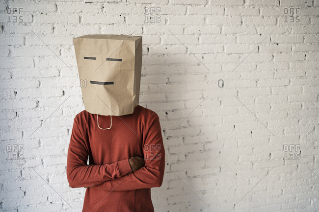Man with arms crossed wearing brown paper bag on face against white brick wall