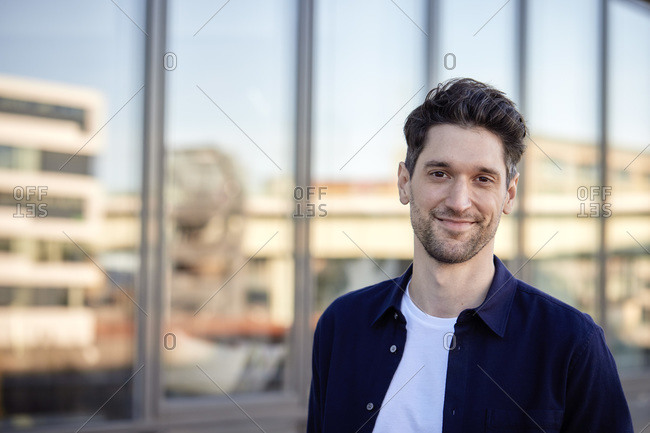 Businessman smiling while standing against building