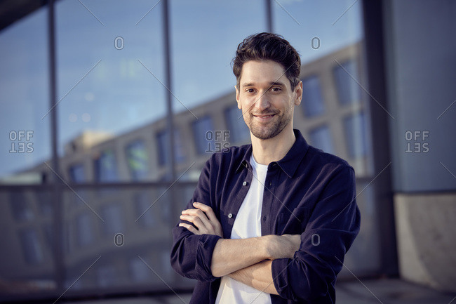 Smiling businessman with arms crossed standing outdoors
