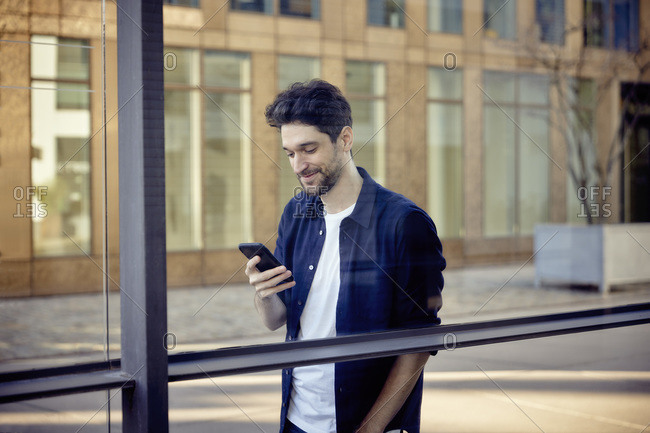 Smiling businessman using mobile phone while leaning on glass wall