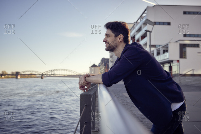 Smiling businessman looking away while leaning on railing