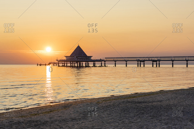 Germany- Mecklenburg-Western Pomerania- Heringsdorf- Sandy coastal beach at sunrise with Heringsdorf Pier in background