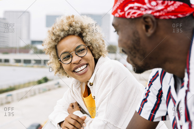 Female friend smiling while looking at man standing in city