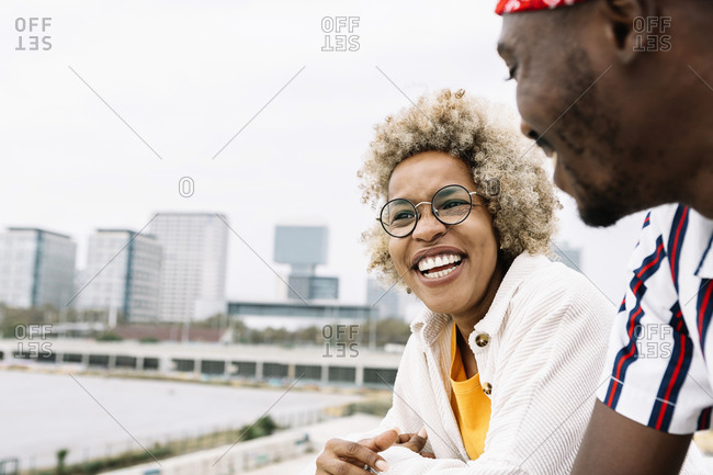 Smiling woman looking away while standing with friend at city