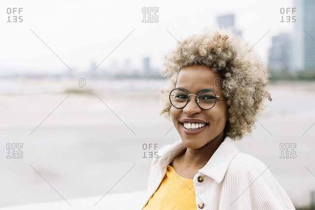 Woman wearing eyeglasses smiling while standing outdoors