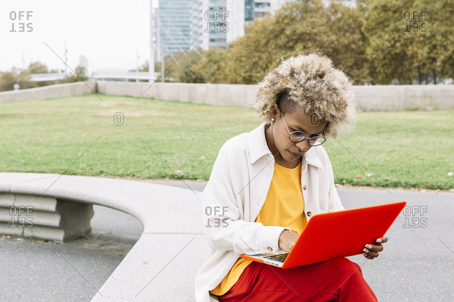 Curly hair woman using laptop while sitting on bench