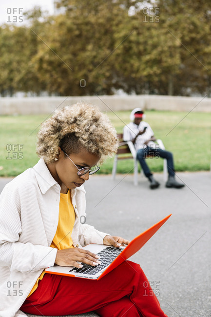 Curly hair woman using laptop while sitting outdoors