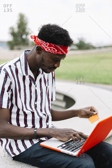 Mid adult man with credit card doing shopping on laptop while sitting outdoors