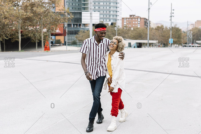 Smiling man walking with arm around female friend on footpath in city