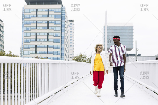 Mid adult woman and man talking while walking on bridge in city