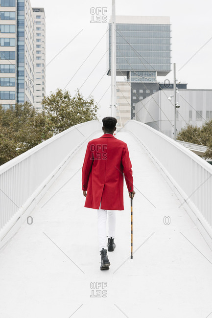 Man wearing red jacket walking with walking cane on bridge in city