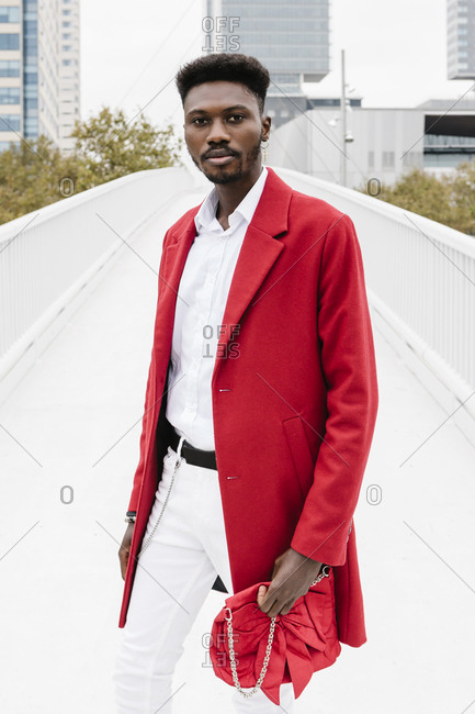 Stylish man wearing red jacket while standing on bridge