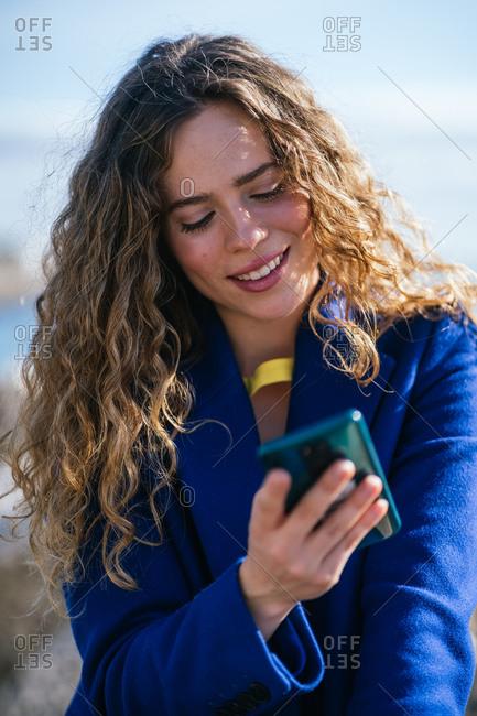 Happy stylish woman using smartphone
