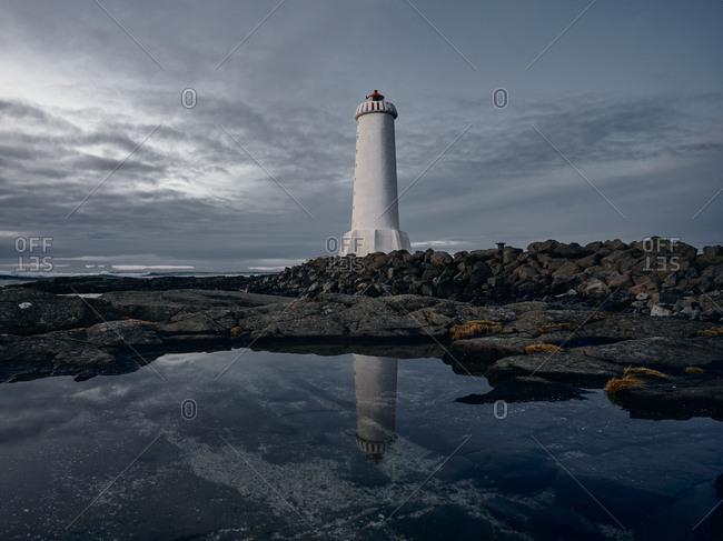 Lighthouse against gray cloudy sky