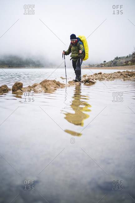 Hiker crossing river on shoal
