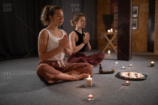 Girlfriends meditating near candles and incense