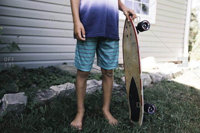 faceless image of child holding skateboard