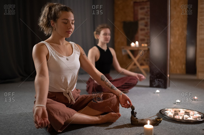 Woman meditating with friend near candles