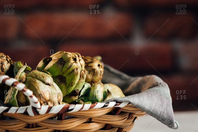 Wicker basket full of organic artichokes
