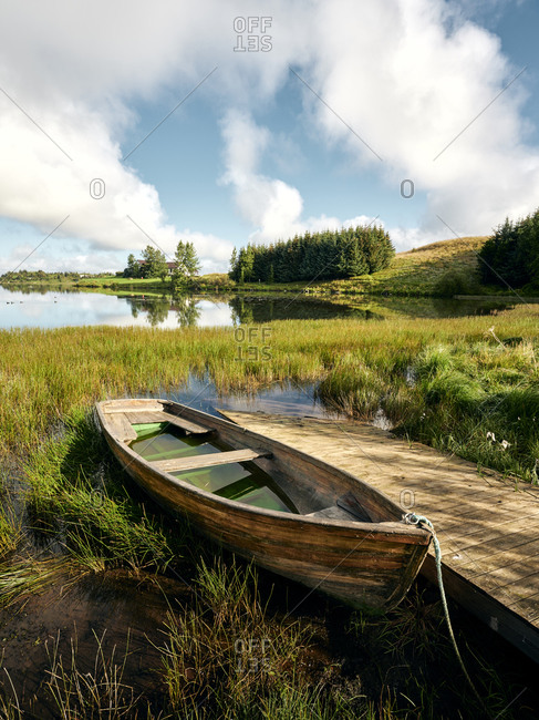 Abandoned boat near pier in countryside