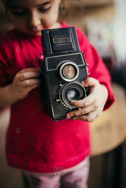 Little girl setting old analog camera.