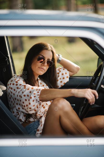 Smiling woman sitting in vintage car.