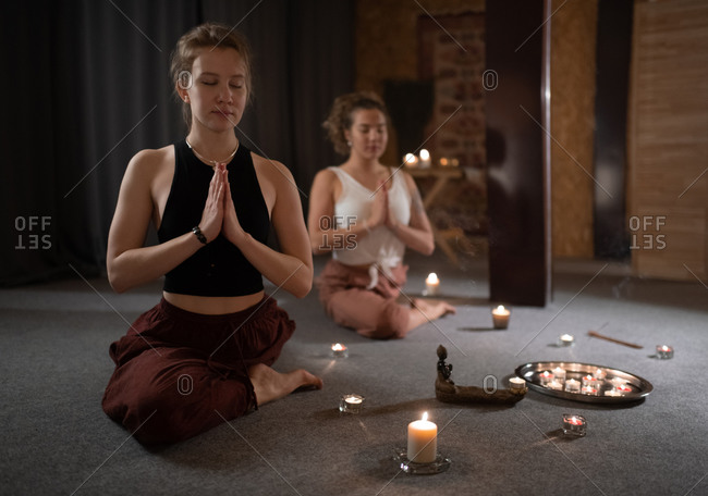 Women meditating in Half Pigeon pose