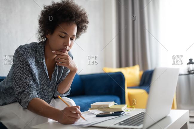 Black woman thinking over tax bills
