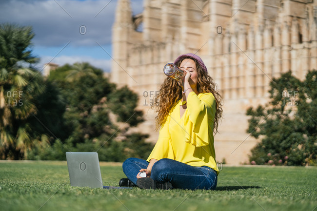 Young woman drinking water on lawn