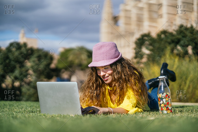 Young woman using laptop on grass