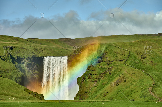 Majestic rainbow against waterfall in green mountains
