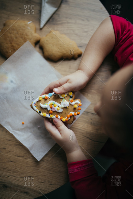 Little girl holding decorated cookie from above.