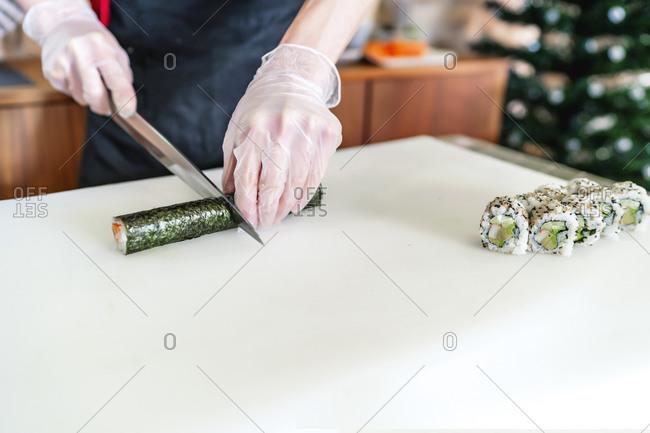 Japanese expert sushi chef cutting sushi roll