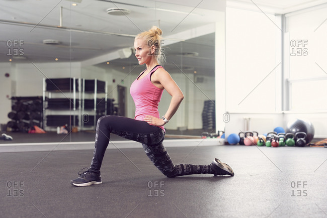 Sporty woman stretching legs in fitness club