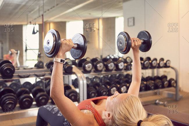 Woman doing bench press workout with weights