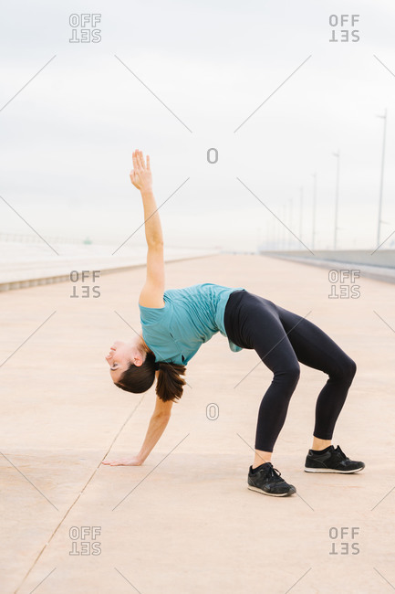 woman practicing Triangle Pose on the street