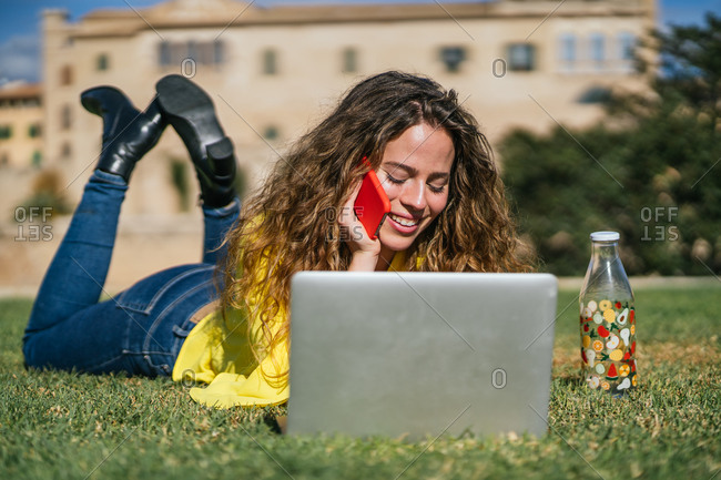 Young female speaking on smartphone on lawn