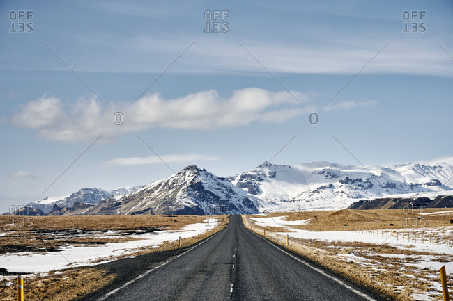 Empty road in terrain with snowy mountains