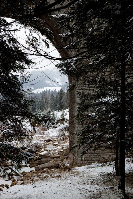 beneath stone bridge in winter with snow