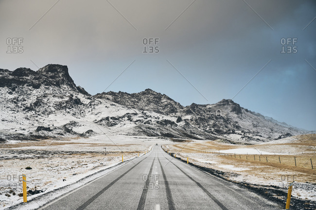 Snowy road and mountains on overcast day
