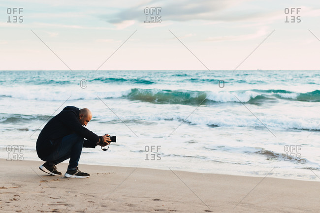 Man Photographing On A Beach At Sunset