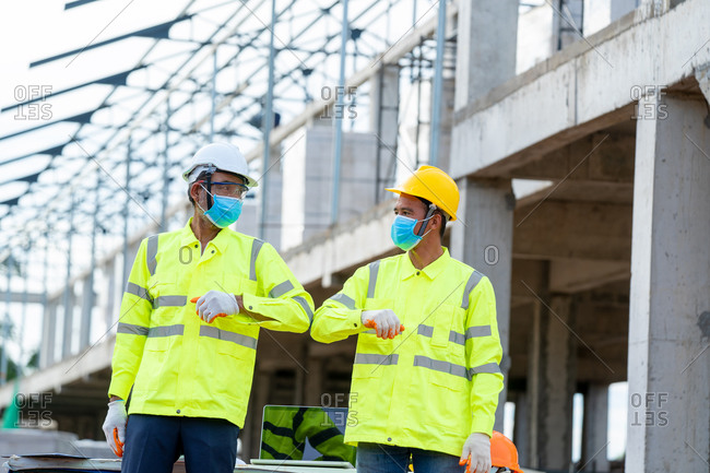 Construction engineer greeting with elbow while wearing protection
