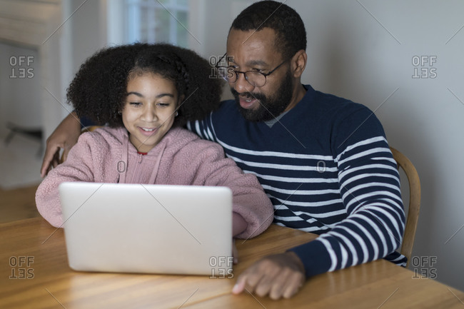 African-American father and bi-racial tween daughter on laptop